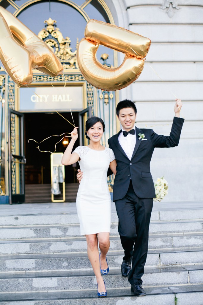 bride-and-groom-holding-giant-gold-letter-balloons-after-ceremony